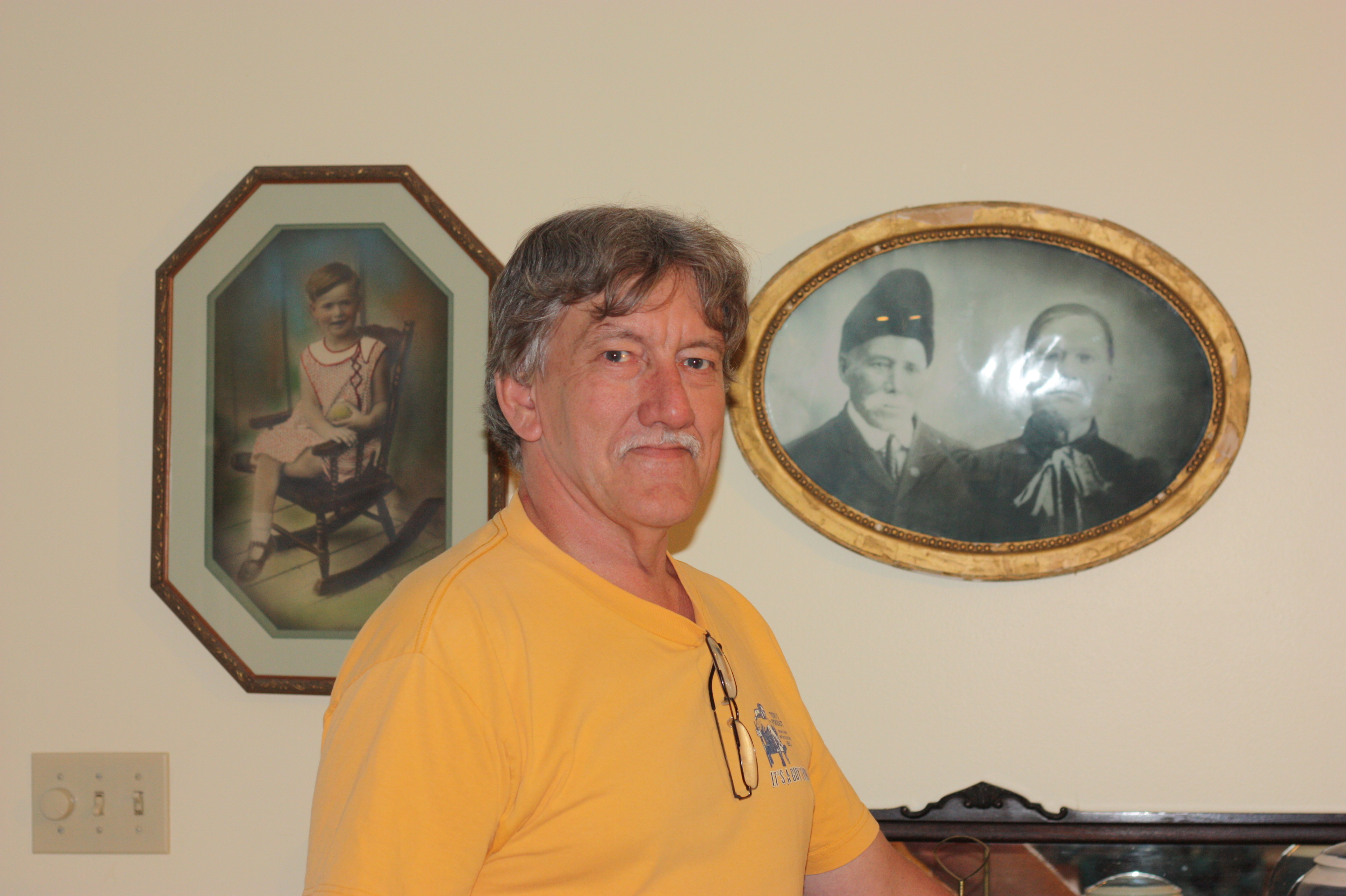 Here's Don at his home. He's standing in front of some old photos on his dining room wall. The photo on the left is his aunt, Jeannine Miller who's now 87. The other photo  is Don's wife Georgette's great-great grandparents.
